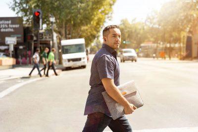 Man carrying laptop case walking across road