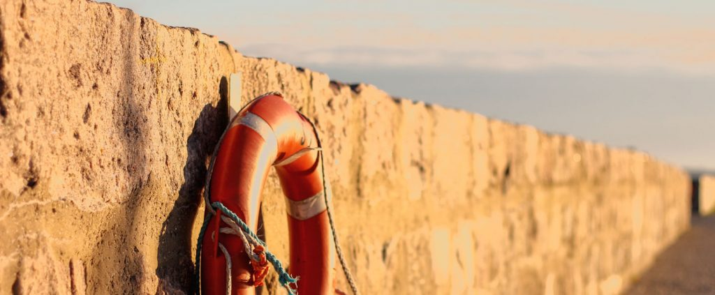 Beach buoy on a stone seawall