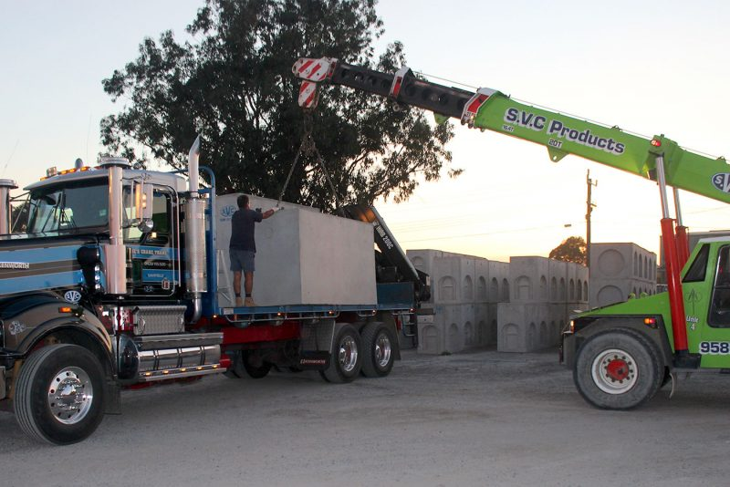SVC crane lifting a large precast concrete pit onto a delivery truck.